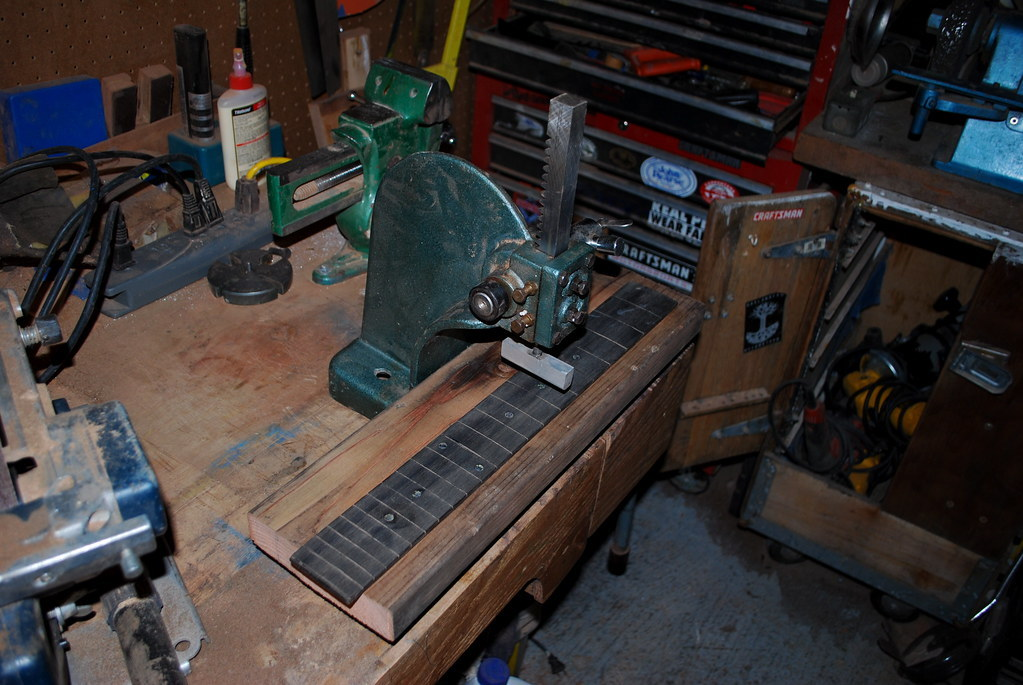 A small arbor press being used to press frets into the neck of a guitar.