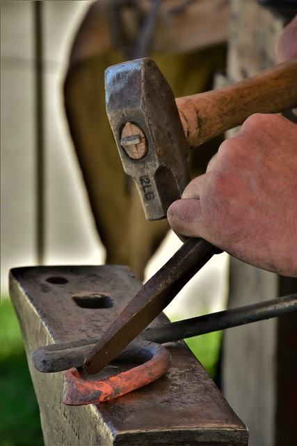 A Blacksmith at the Baker City annual Miner's Jubilee uses a blacksmith chisel not to punch a hole, but to shape a piece of work. Image source