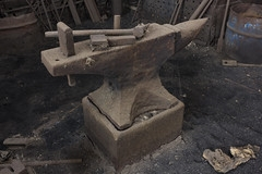 A dusty anvil with two hardy tools lying on top. Image source