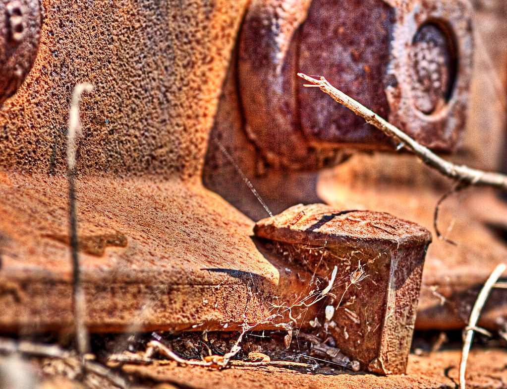 A rusty dog head Railroad spike holds down a piece of track Image Source